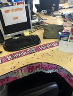 Decorated office desk with 21st brithday banner